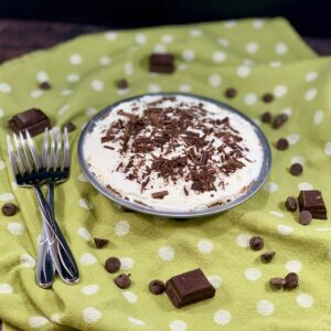 Chocolate Cream Pie with 2 forks surrounded by chocolate on a green polka dot towel.