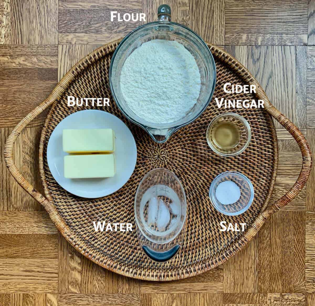Pie crust ingredients in glass bowls on a wooden tray.