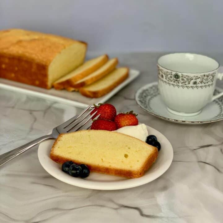 Orange Vanilla Pound Cake plated sliced with cream and berries, sliced loaf & cup in background