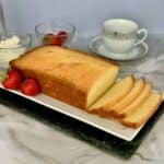 Orange Vanilla Pound Cake loaf sliced with cream, strawberries, & cup