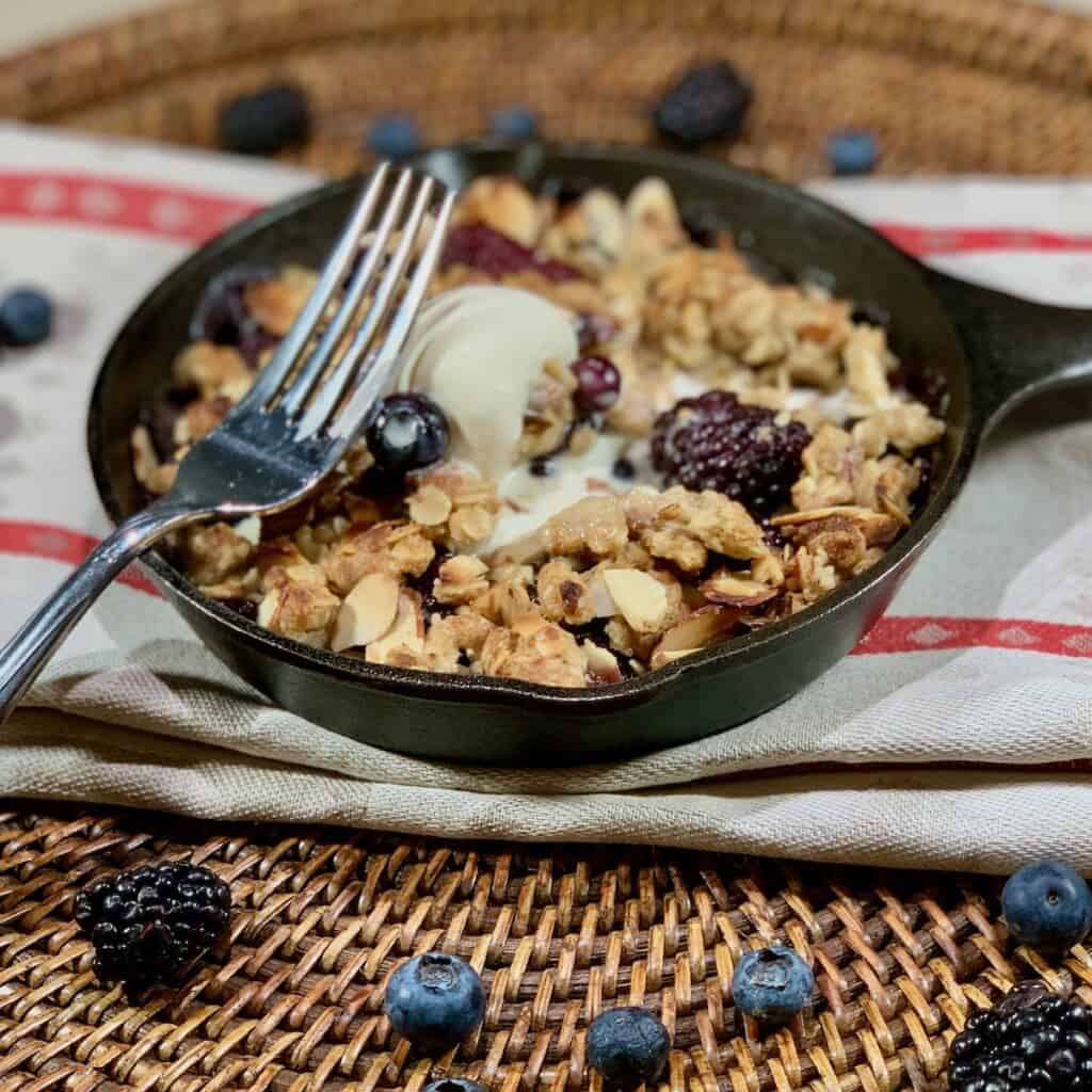 Skillet Berry Crisp on towel with fork closeup