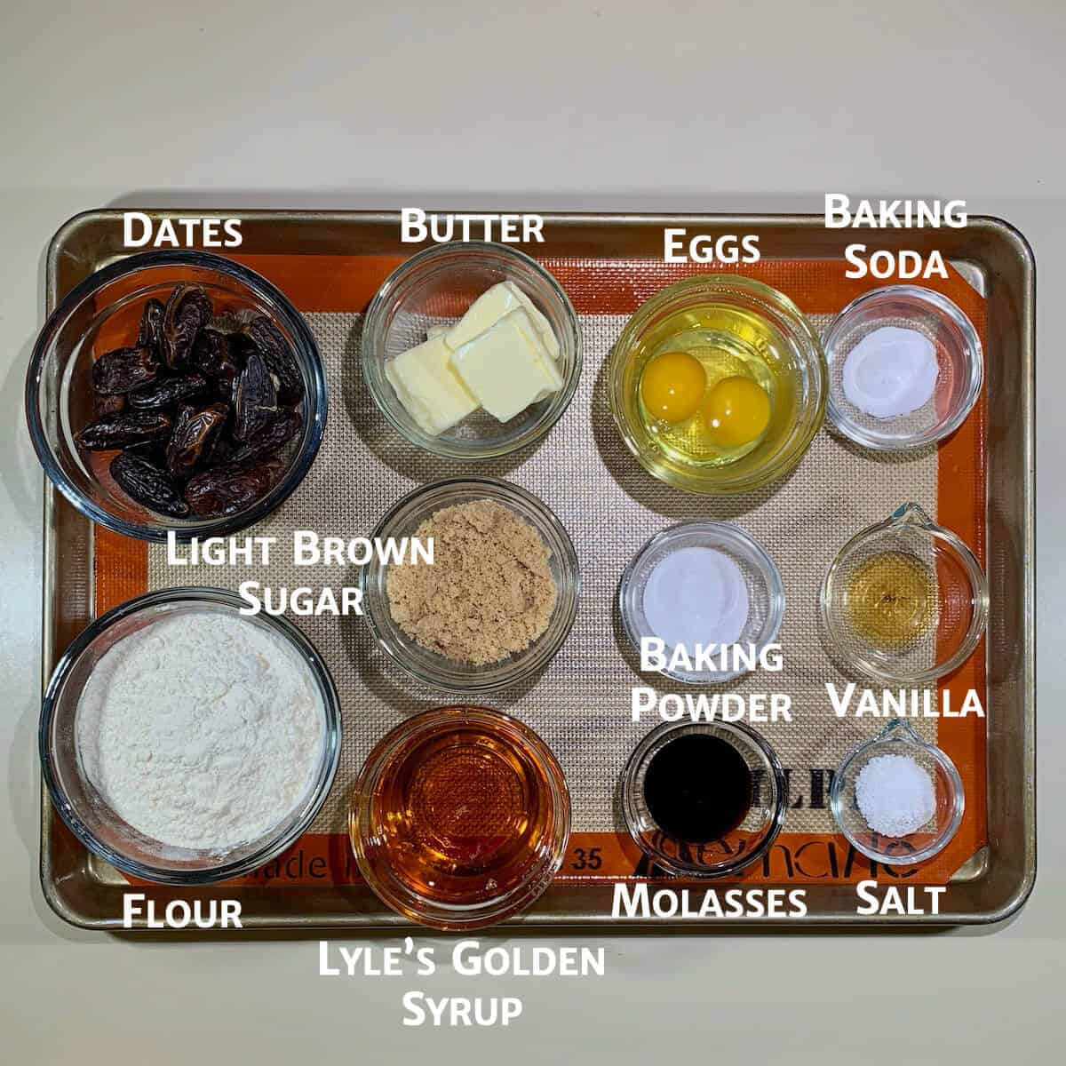 Sticky Toffee Pudding cake ingredients portioned in glass bowls on a baking pan.