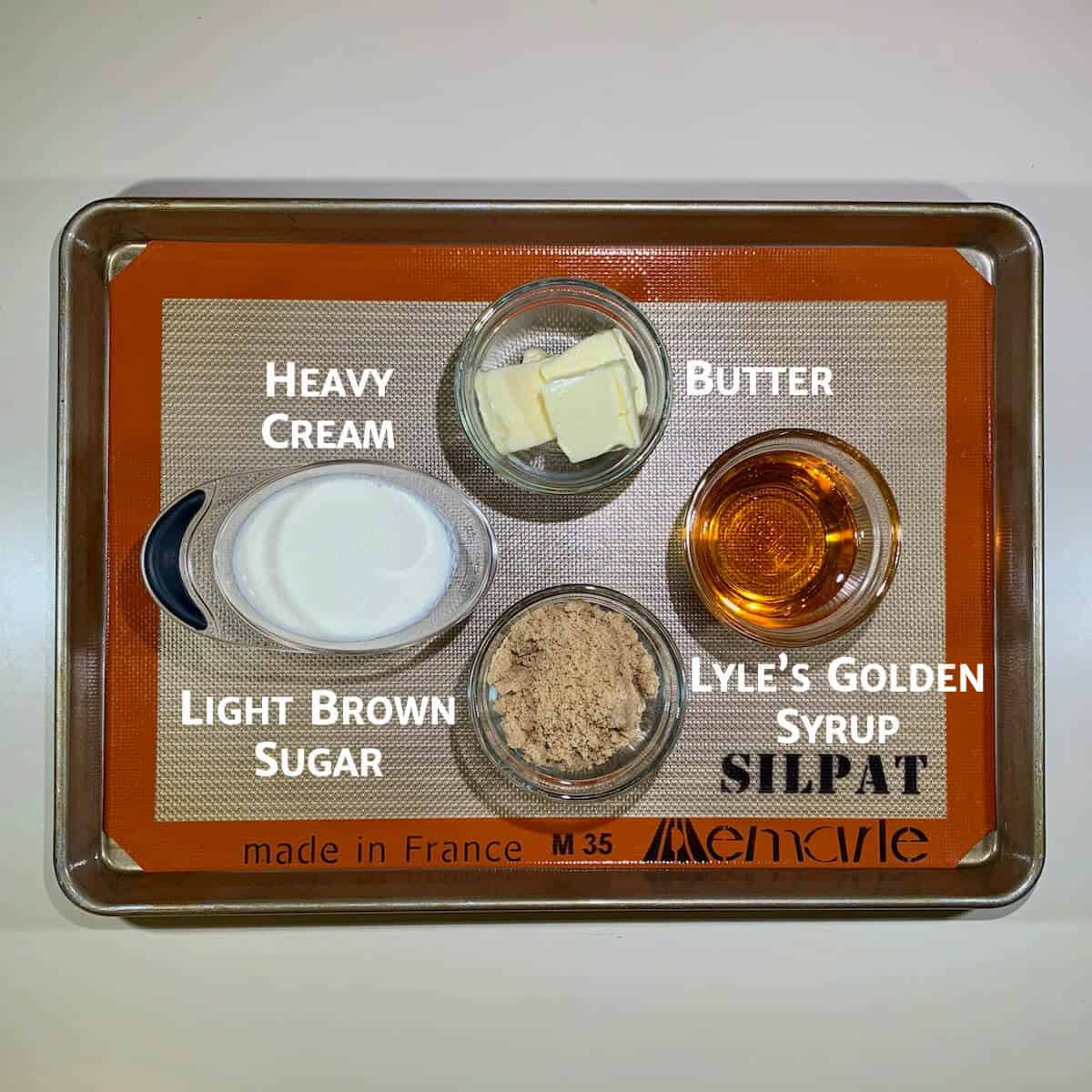 Toffee sauce ingredients portioned in glass bowls on a baking pan.
