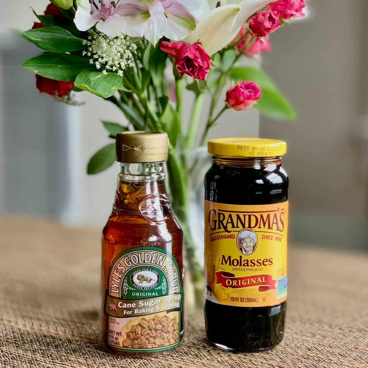 Lyle's Golden Syrup & Grandma's molasses on table with flowers.