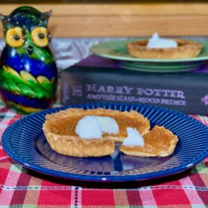 Treacle Tart sliced & plated on blue plate with tart on green plate on book & glass owl in background