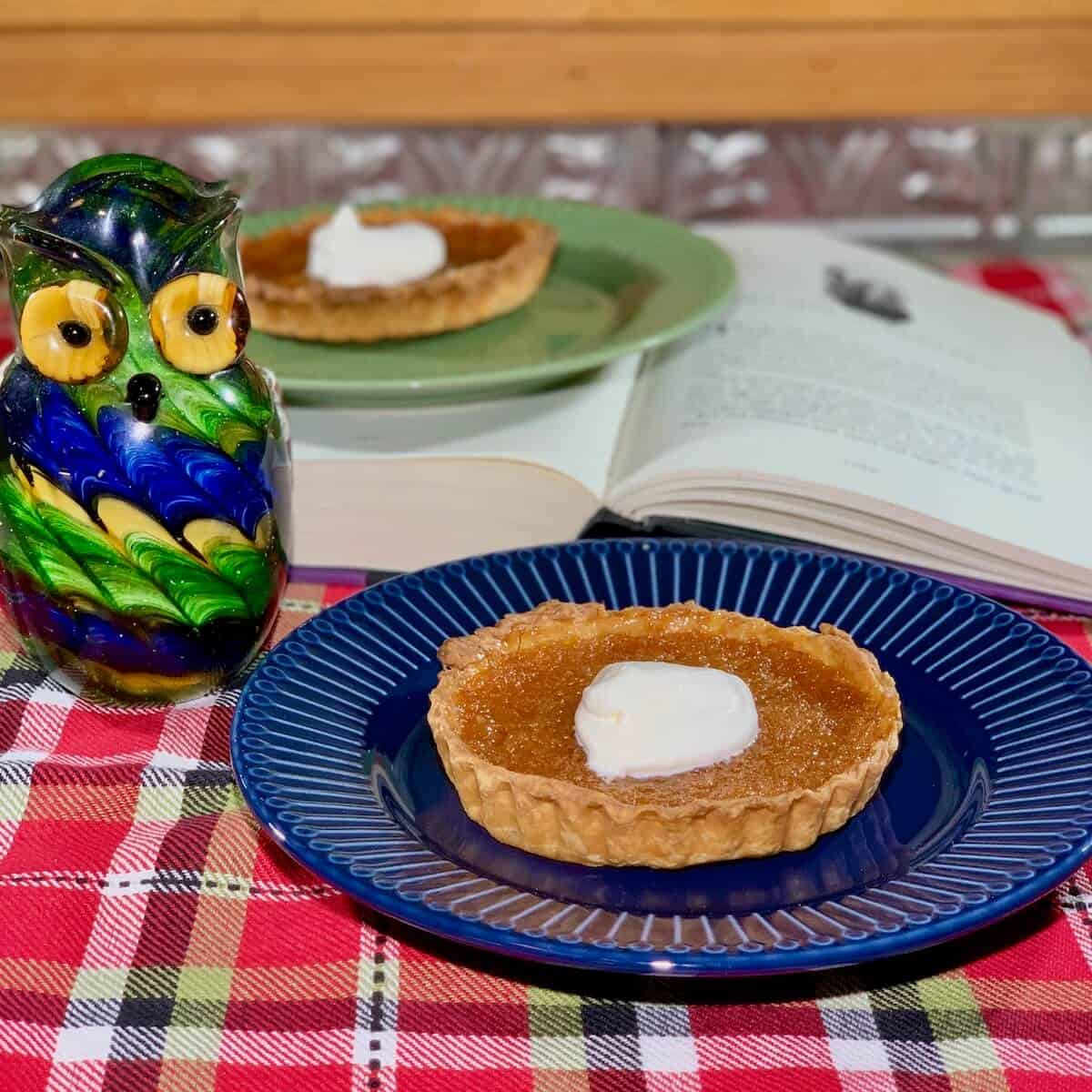 Treacle Tart on blue plate with tart on green plate on open book & glass owl in background.