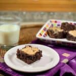 Whiskey Marshmallow Brownies plated with milk and extras behind angle view