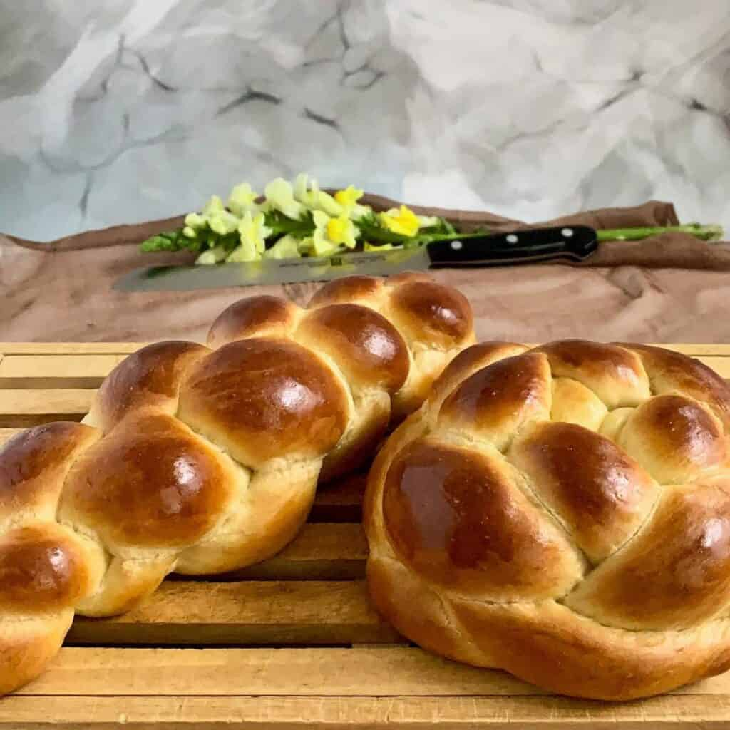 four-strand oblong and round challah on a cutting board