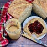 Peanut Butter with bitten open face sandwich and multigrain bread overhead