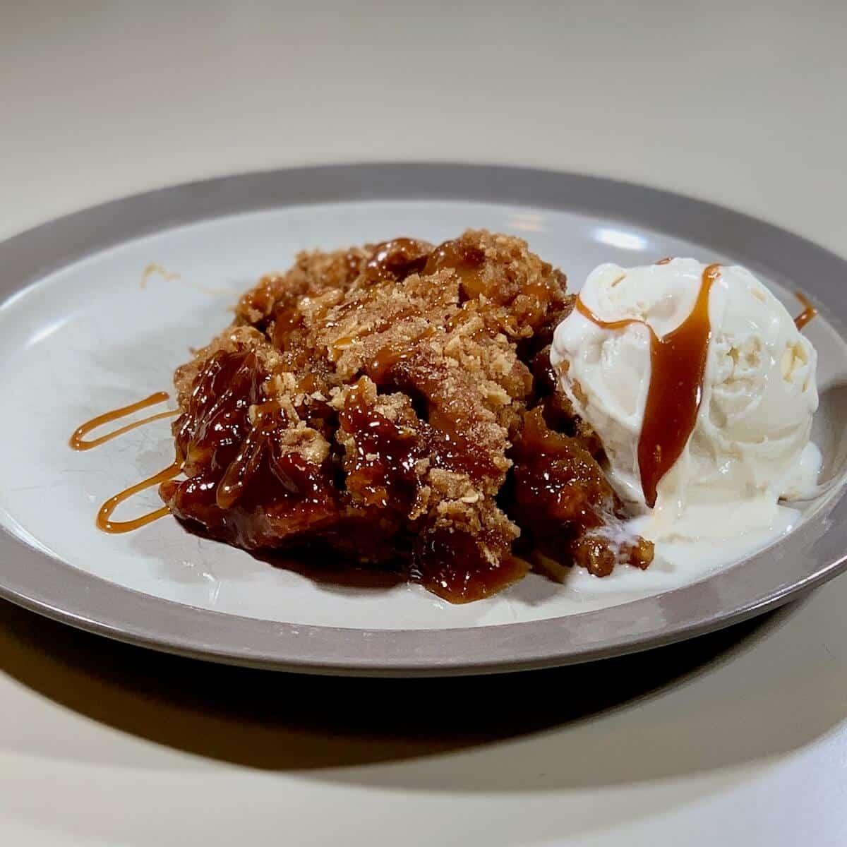 Apple Crisp on a grey-rimmed white plate with vanilla ice cream & caramel sauce on the side.