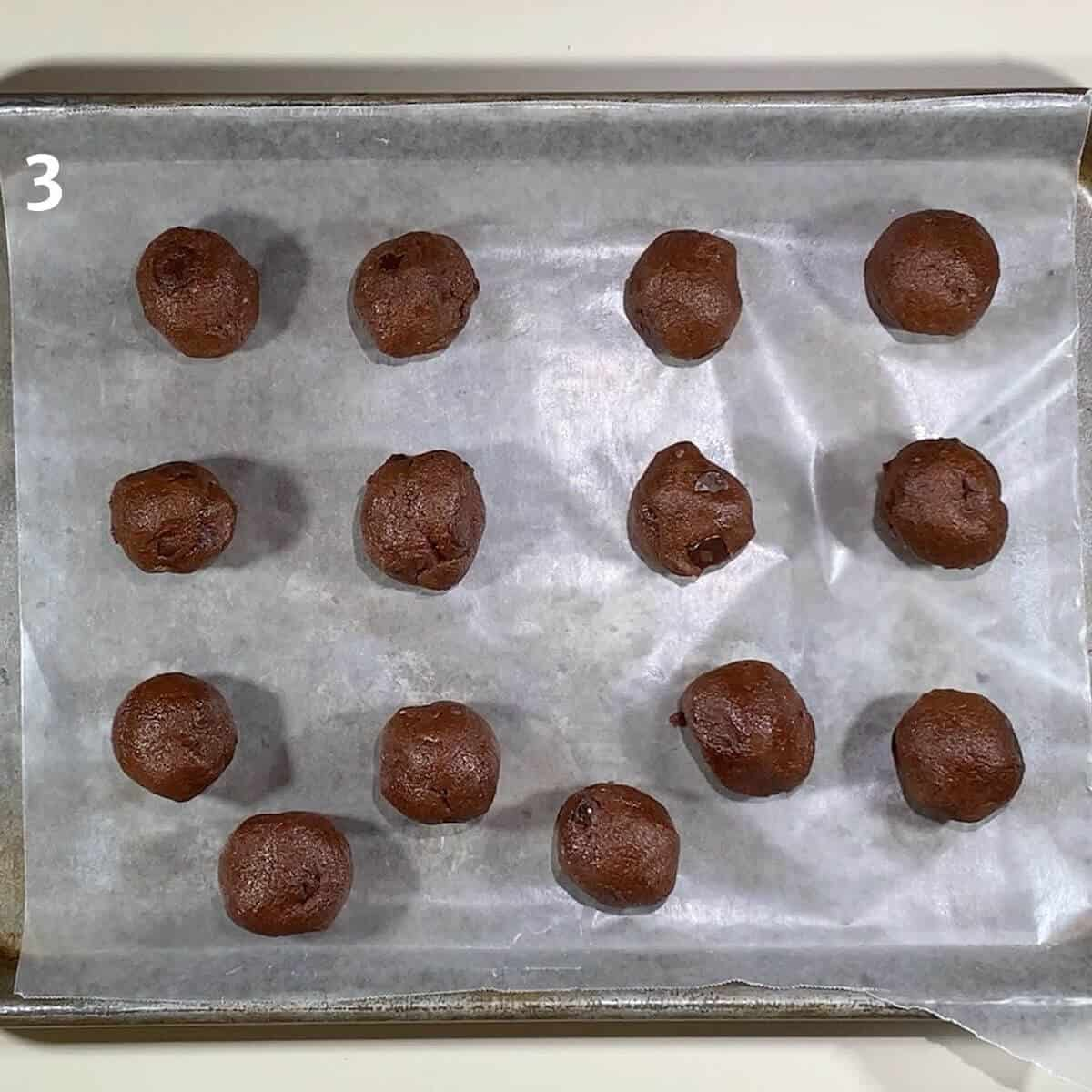Chocolate Chocolate Chip cookie dough portions on wax paper lined tray for freezing.