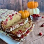 Glazed Orange Cranberry Bread sliced closeup with pumpkins & cranberries