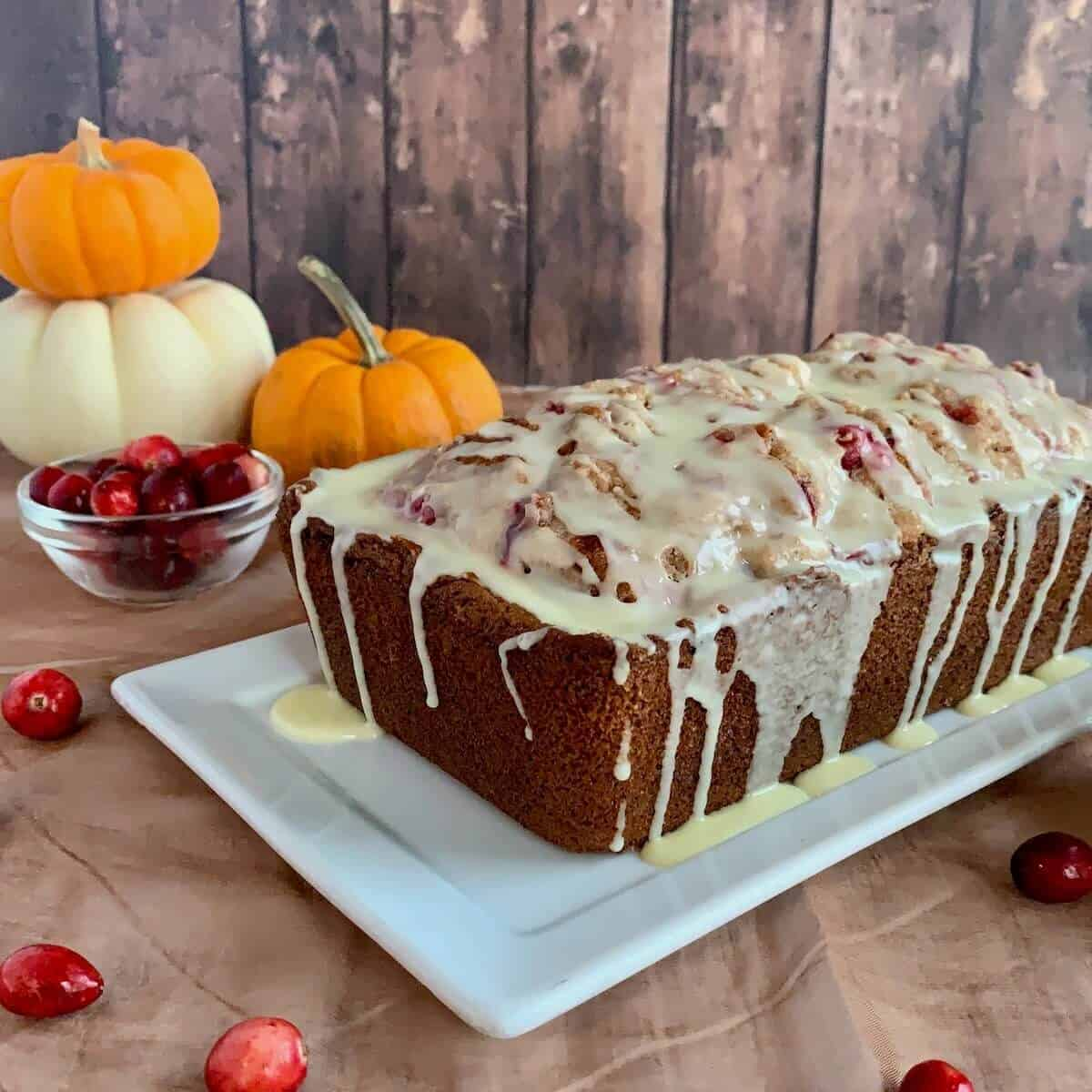 Glazed Orange Cranberry Bread on a white plate with pumpkins & cranberries in background.