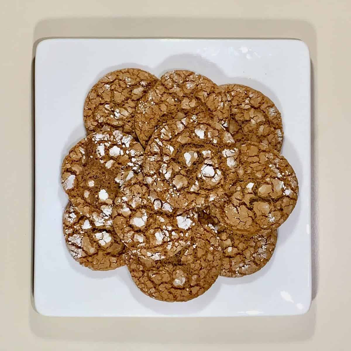 Molasses cookies stacked on white plate from overhead.