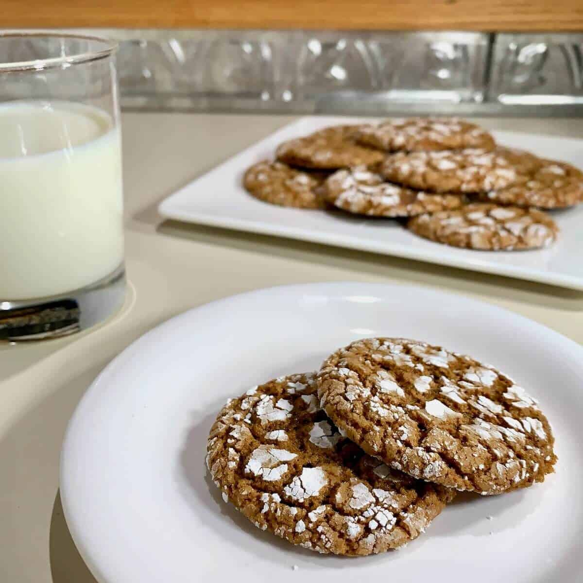Molasses cookies on a white plate with more cookies and a glass of milk in background.