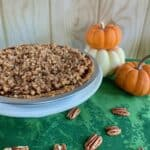 Praline Pumpkin Pie whole with pumpkins behind