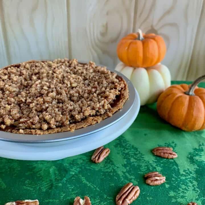 Praline Pumpkin Pie whole with pumpkins behind