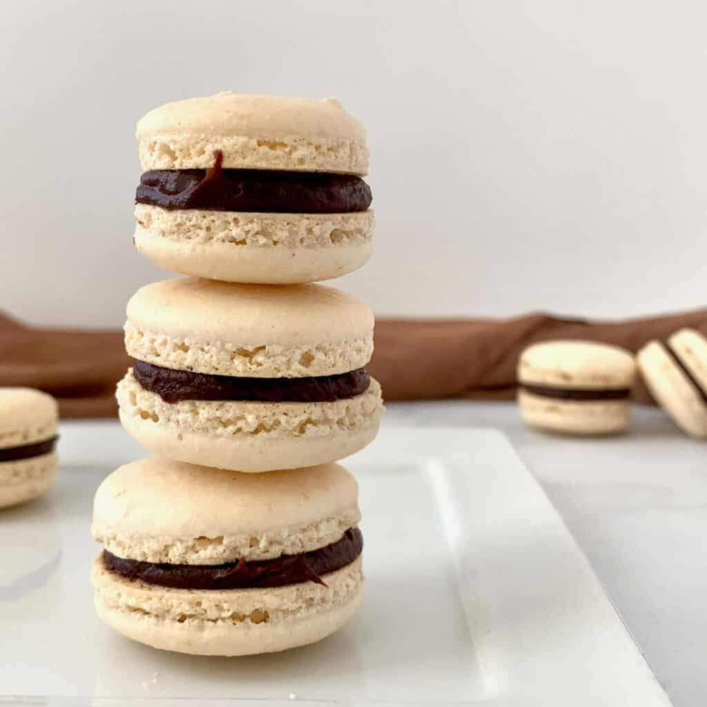 Italian Meringue Macarons stacked on white plate with some in background