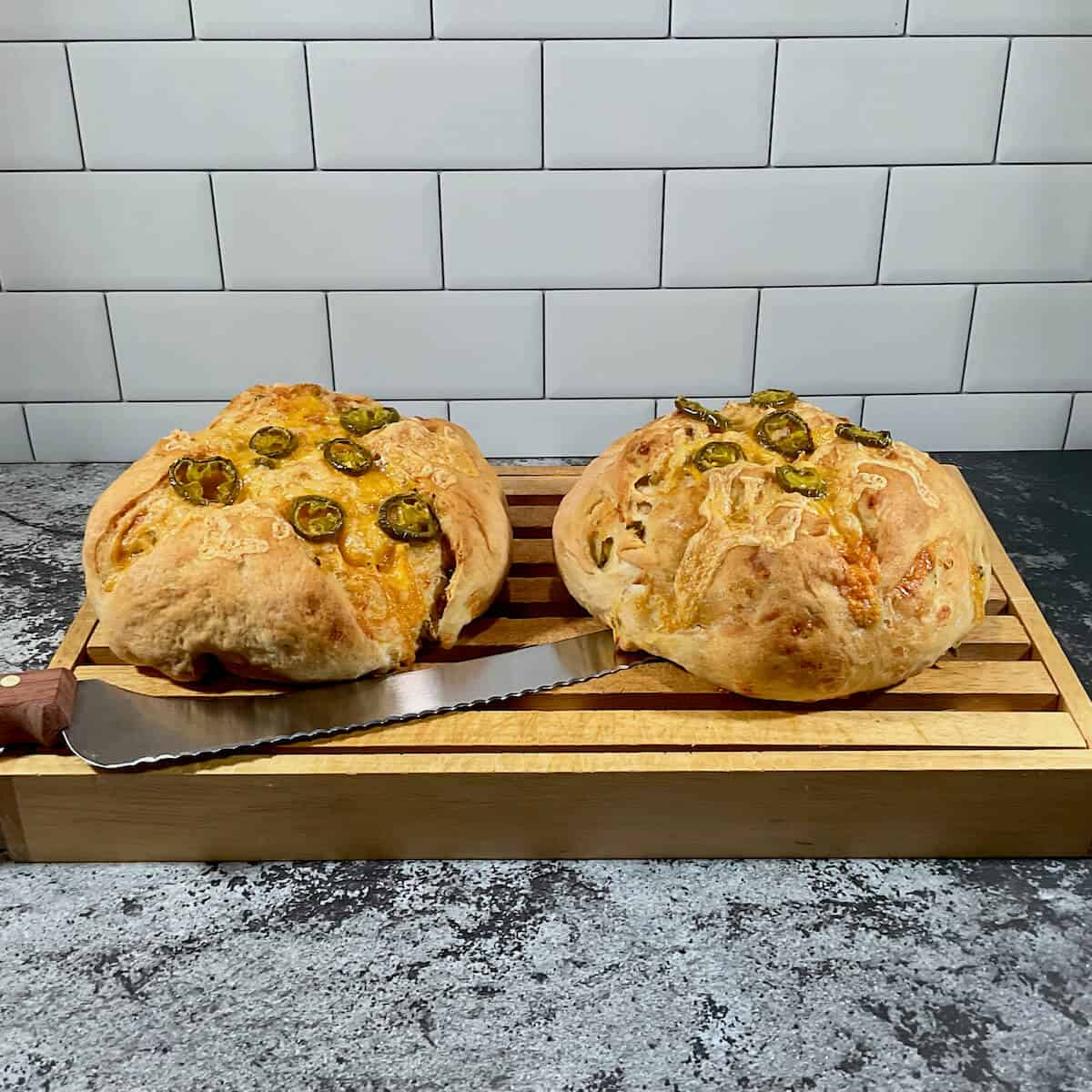 Two loaves of Sourdough Jalapeño Cheddar Bread on cutting board with knife.