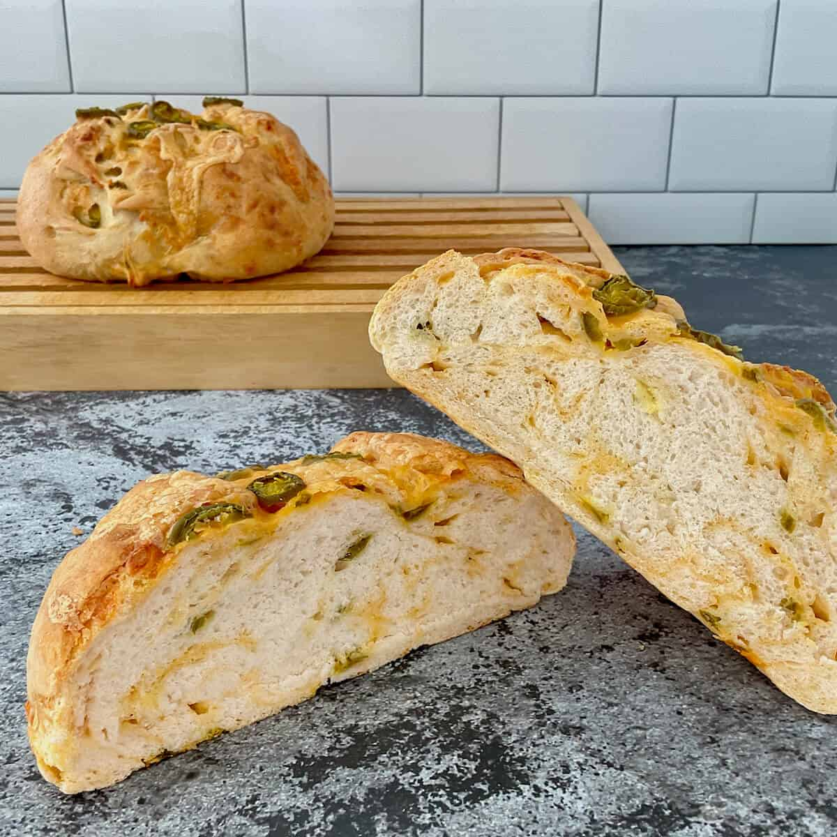Sourdough Jalapeño Cheddar Bread sliced open closeup with loaf behind on cutting board.