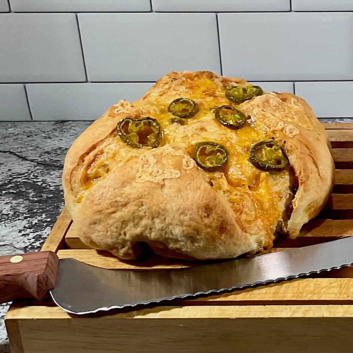 Sourdough Jalapeño Cheddar Bread on cutting board with knife.