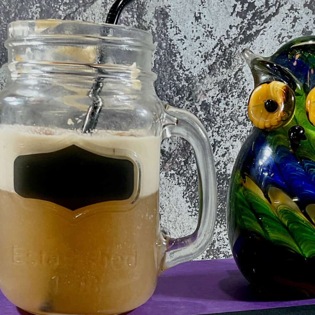 Butterbeer in a mason jar next to a glass owl.