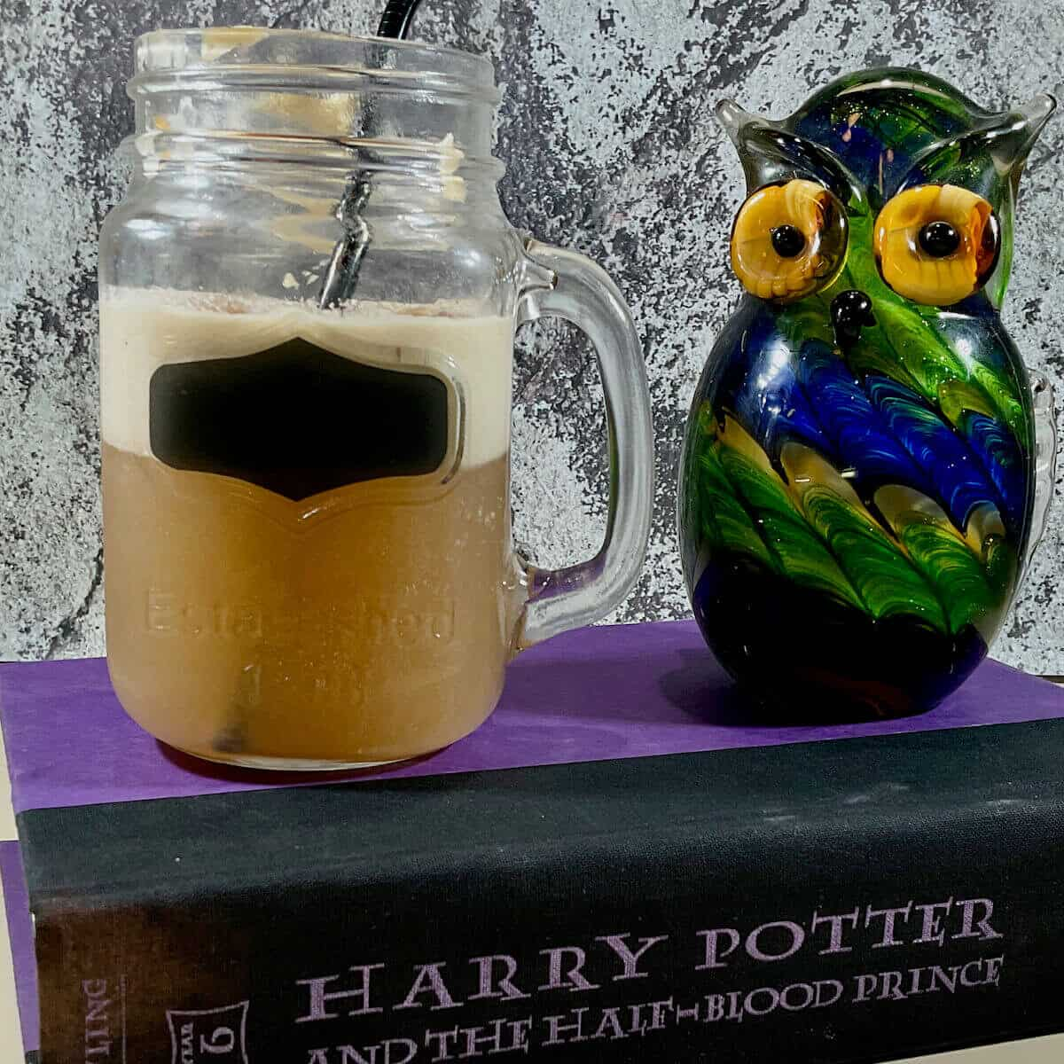 Butterbeer in a mason jar next to a glass owl on a book.