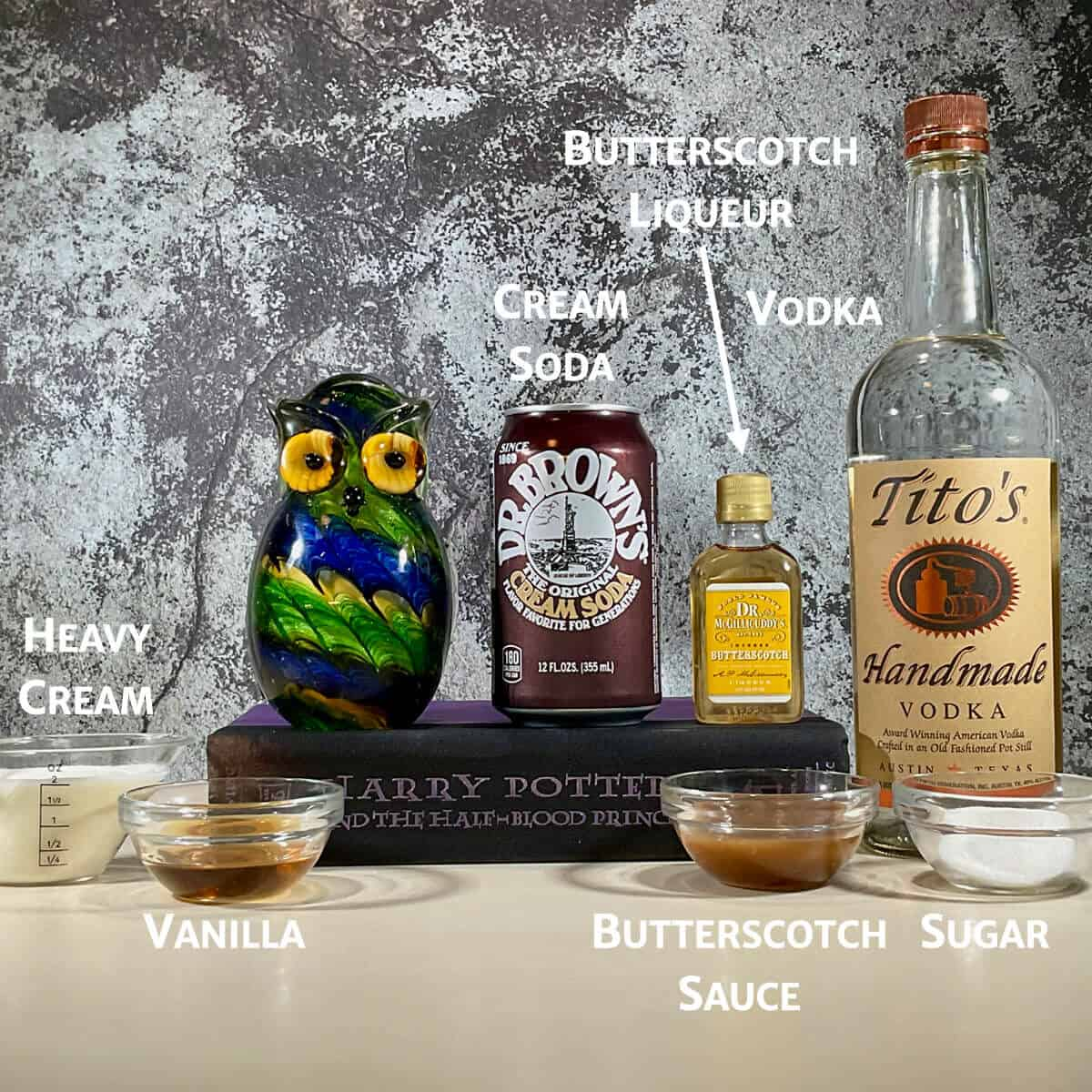 Boozy butterbeer ingredients on a counter with a glass owl & book.