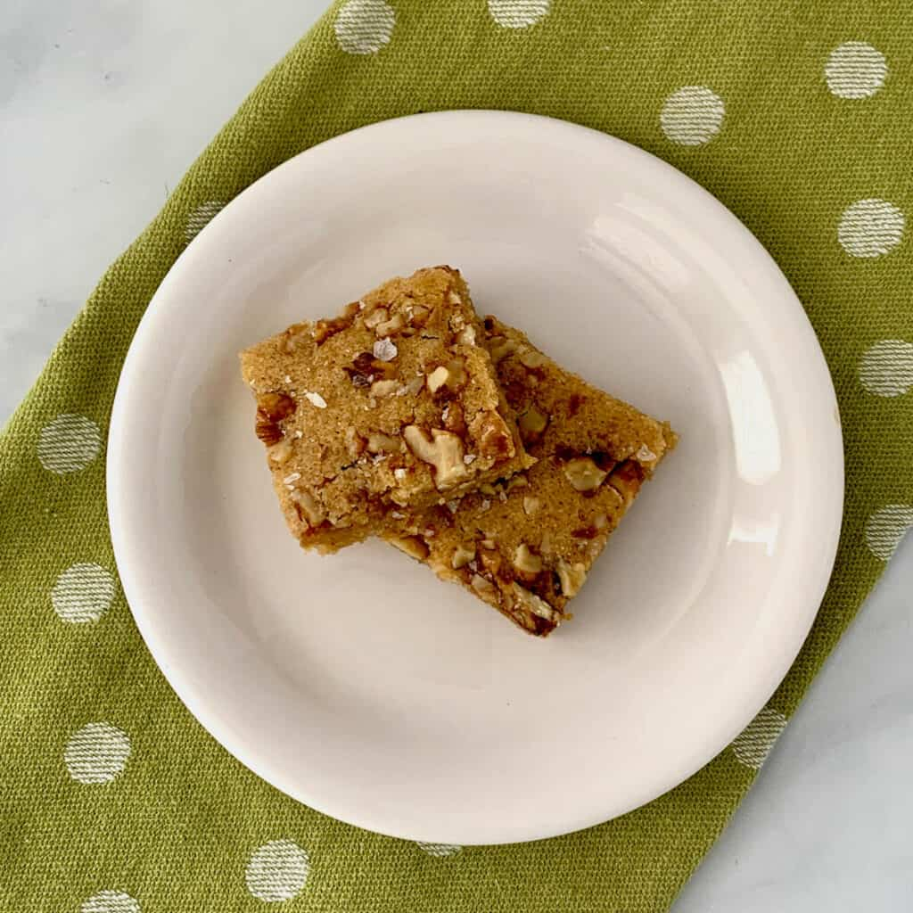 maple walnut bourbon blondies on white plate with green spotted towel closeup from overhead