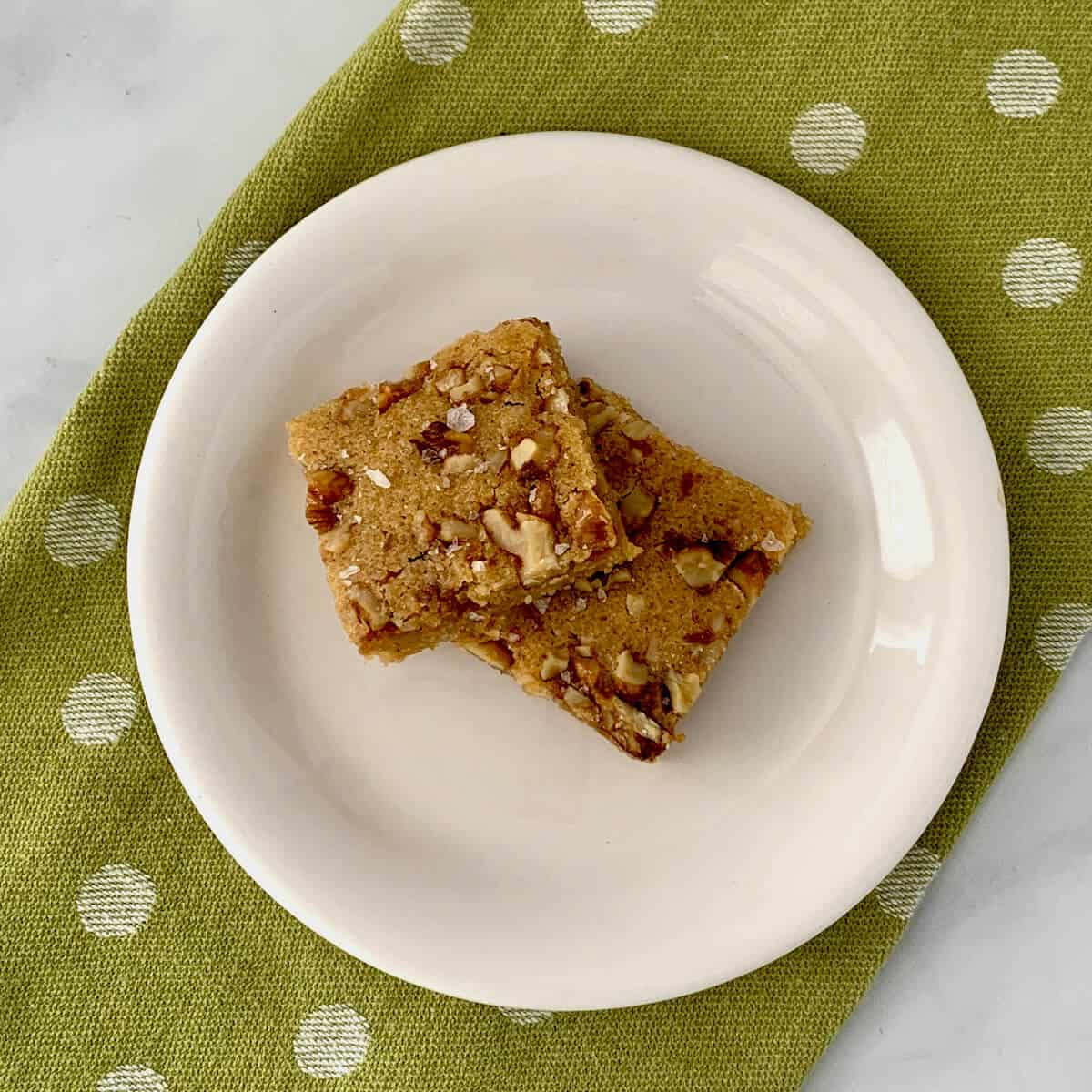Stack of Maple Walnut Bourbon Blondies on a white plate sitting on a green towel with white polka dots from overhead.