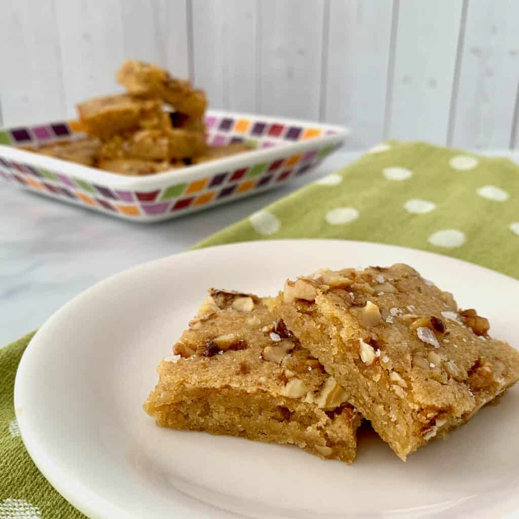 maple walnut bourbon blondies on white plate with green spotted towel & plate of stacked blondies behind