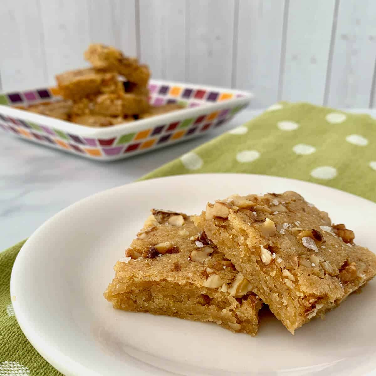 Stack of Maple Walnut Bourbon Blondies on a white plate sitting on a green towel with white polka dots..