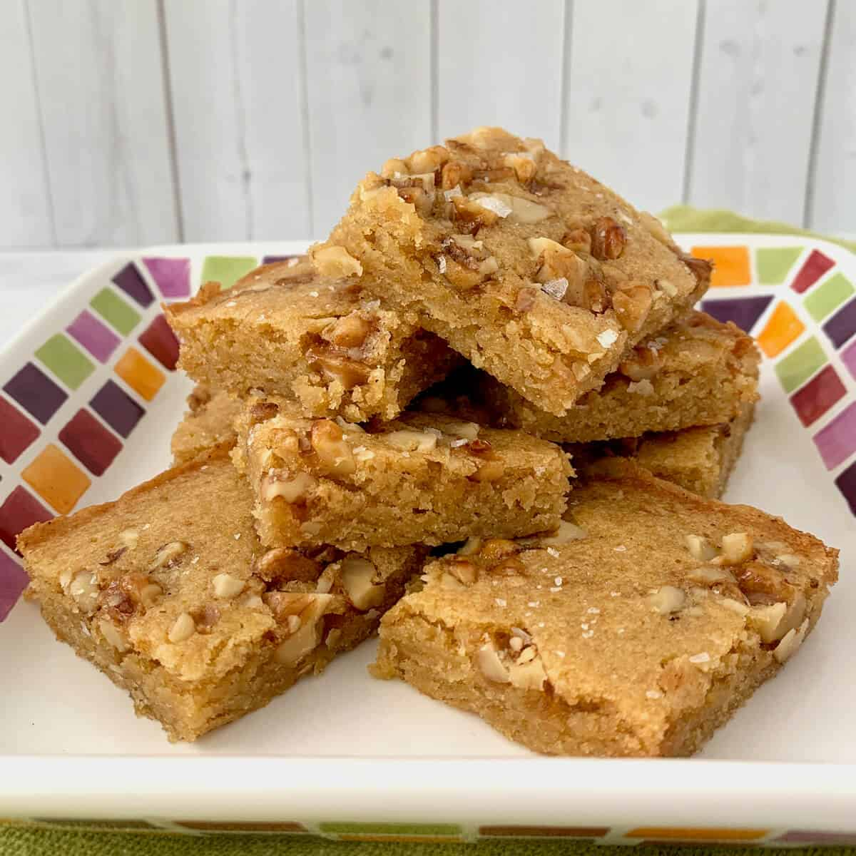 Stack of Maple Walnut Bourbon Blondies on a white plate with multicolored checks.