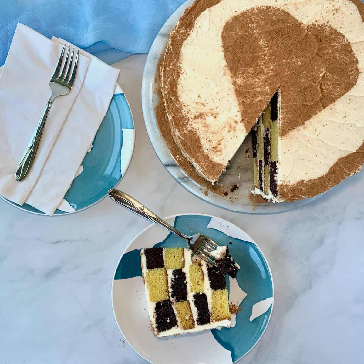 checkerboard cake slice on a blue & white plate with cake on plate and fork in background
