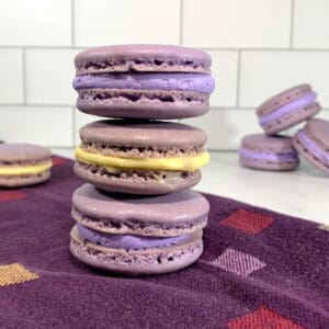 French Macarons with purple buttercream & lemon curd stacked on a purple towel with more in background.