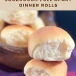two sourdough dinner rolls stacked on a purple checked towel with bowl of rolls in background Pinterest banner