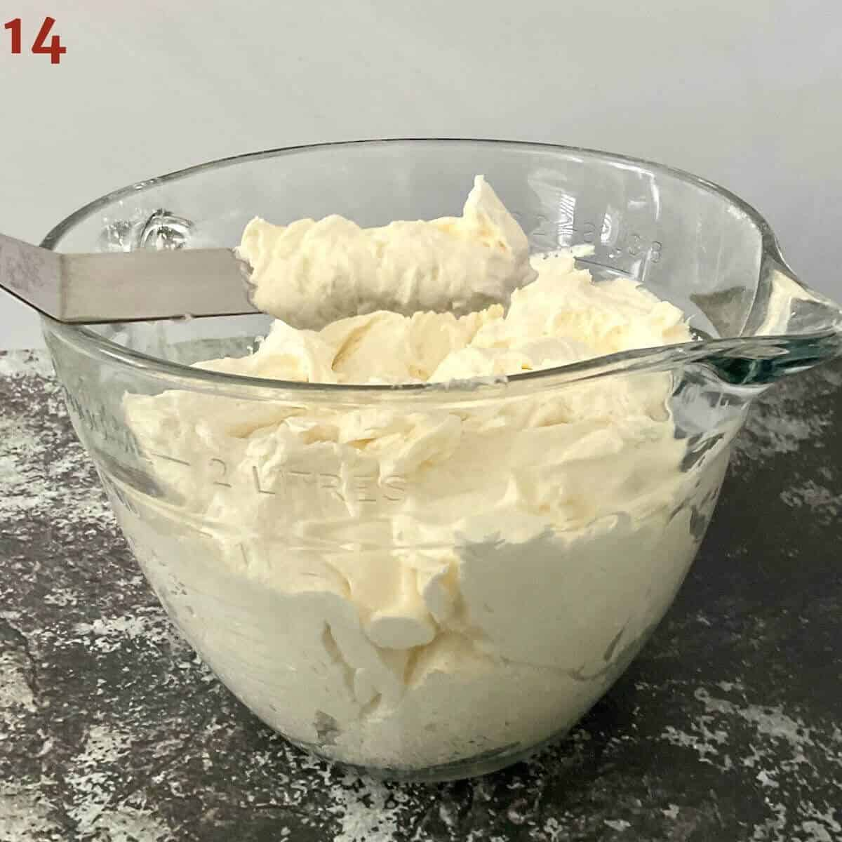 vanilla buttercream in a large glass measuring bowl with some on a spatula