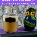 Butterbeer in a mason jar next to a glass owl on a book Pinterest banner.