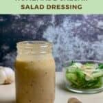 Jar of Caesar salad dressing on a counter with garlic & green salad Pinterest banner.
