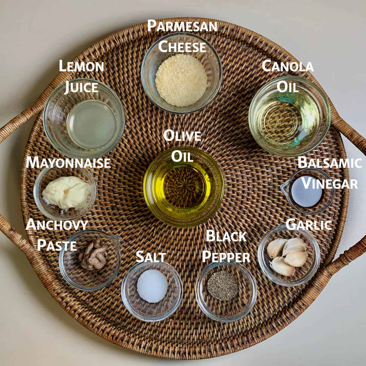 Caesar salad ingredients in glass bowls on a wooden tray.