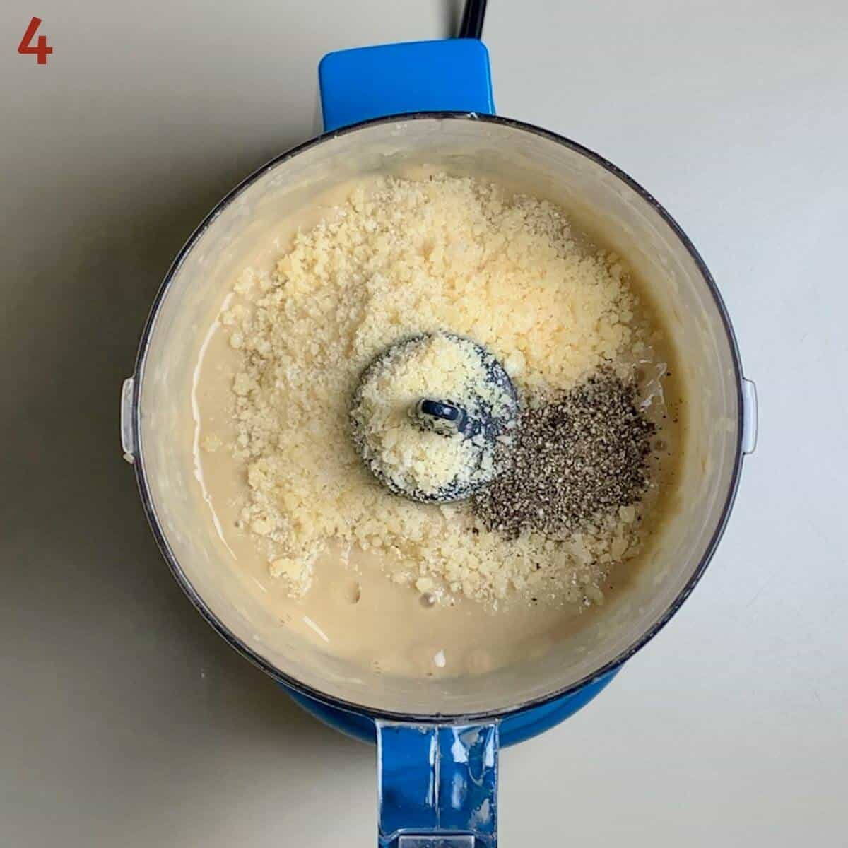 Adding parmesan cheese & black pepper to Caesar salad base in a food processor.