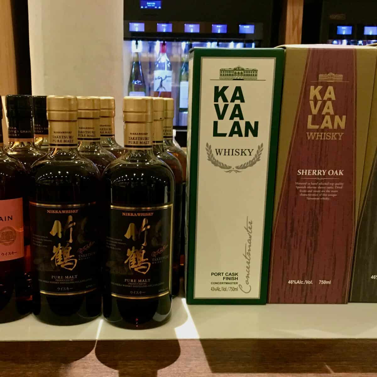 Kavalan & Nikka whisky tasting lineup in boxes & bottles on a counter.