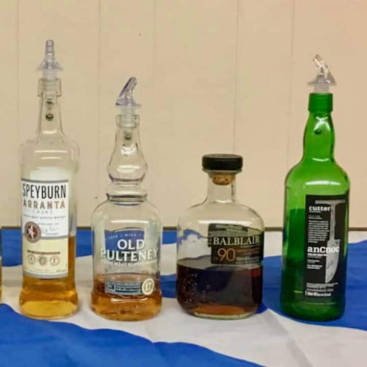 375 Park Ave Spirits Single Malt Scotch Tasting partial lineup in bottles on a Scottish flag.