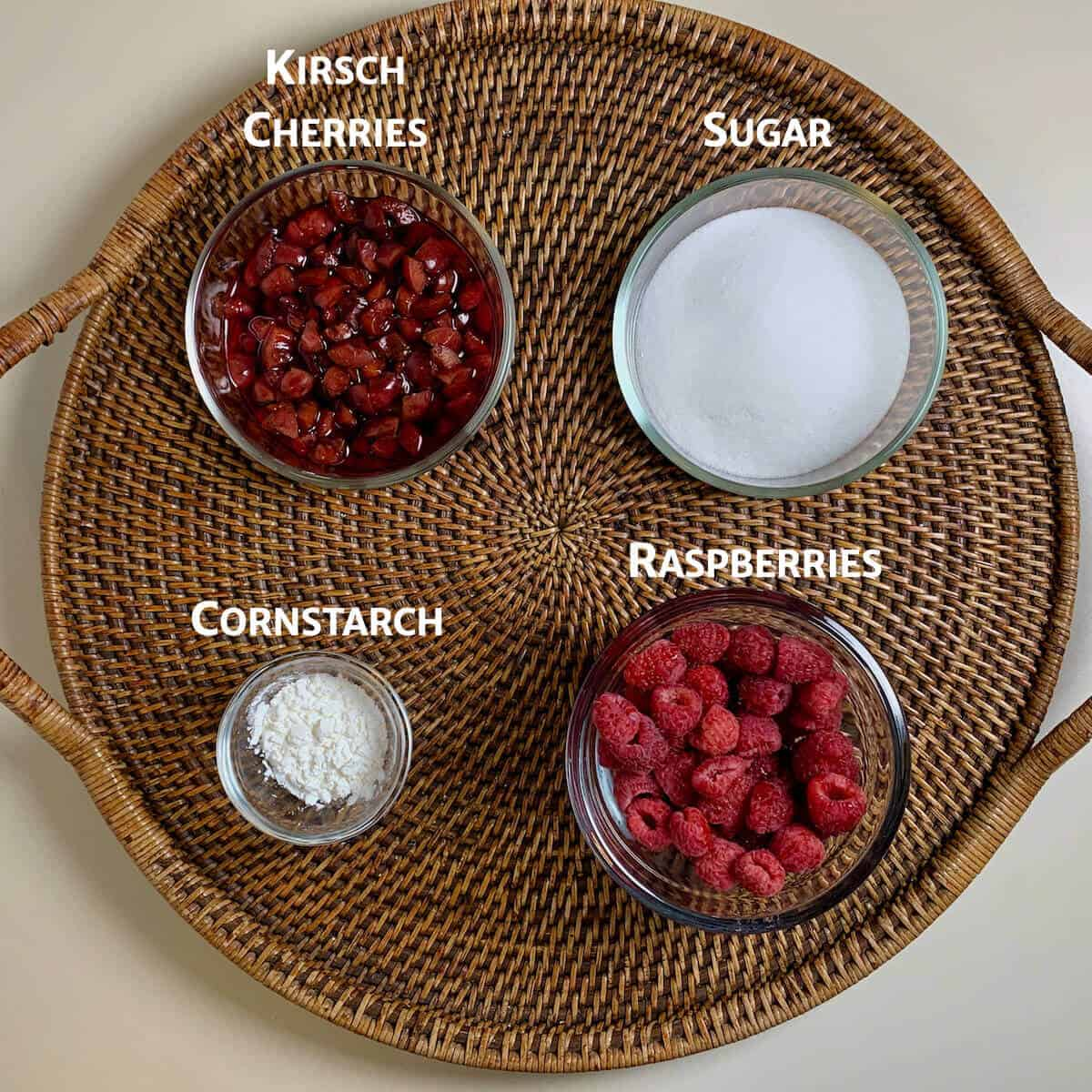Raspberry & Kirsch cherry Jam ingredients on a wooden tray from overhead.