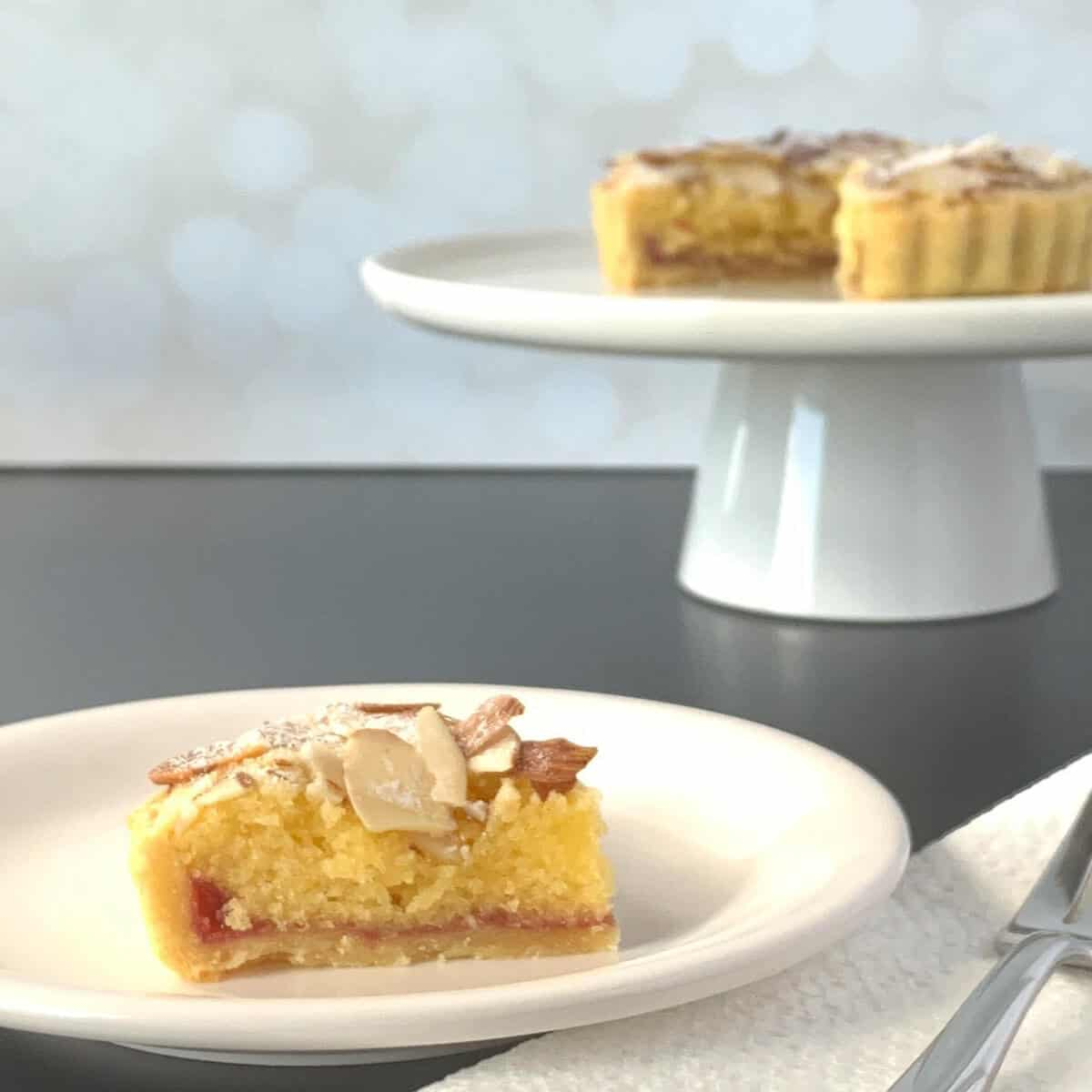 Slice of Bakewell tart on a white plate in front of a sliced tart on a white cakestand.