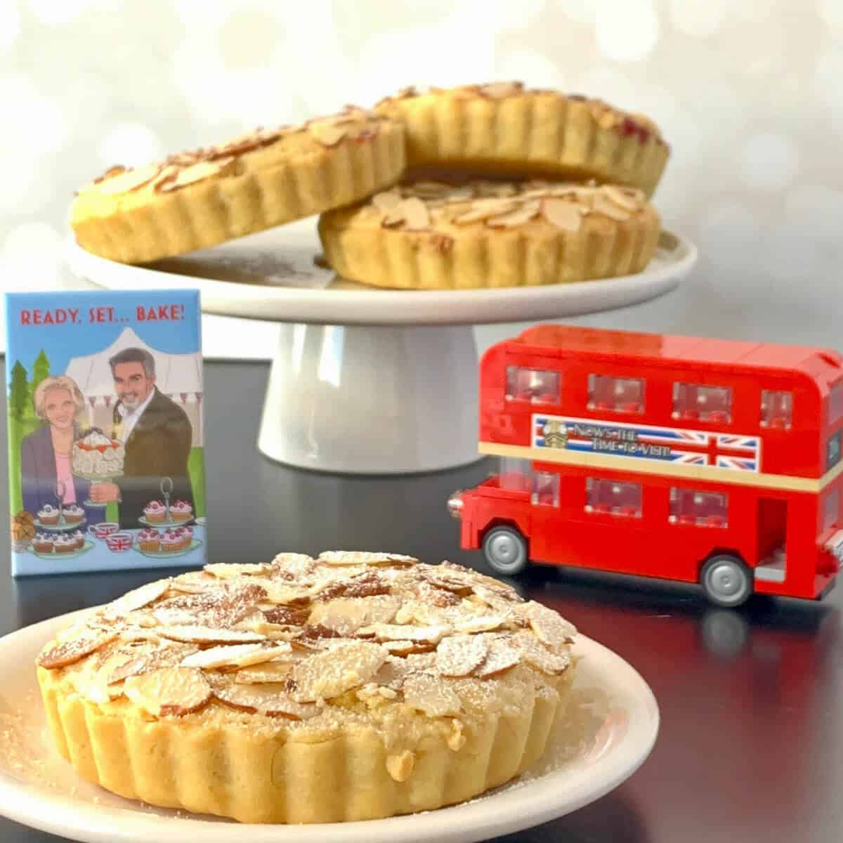 Mini Bakewell Tart on a white plate in front of 3 tarts on a white cake stand, a toy double-decker bus, & a Great British Bakeoff magnet.