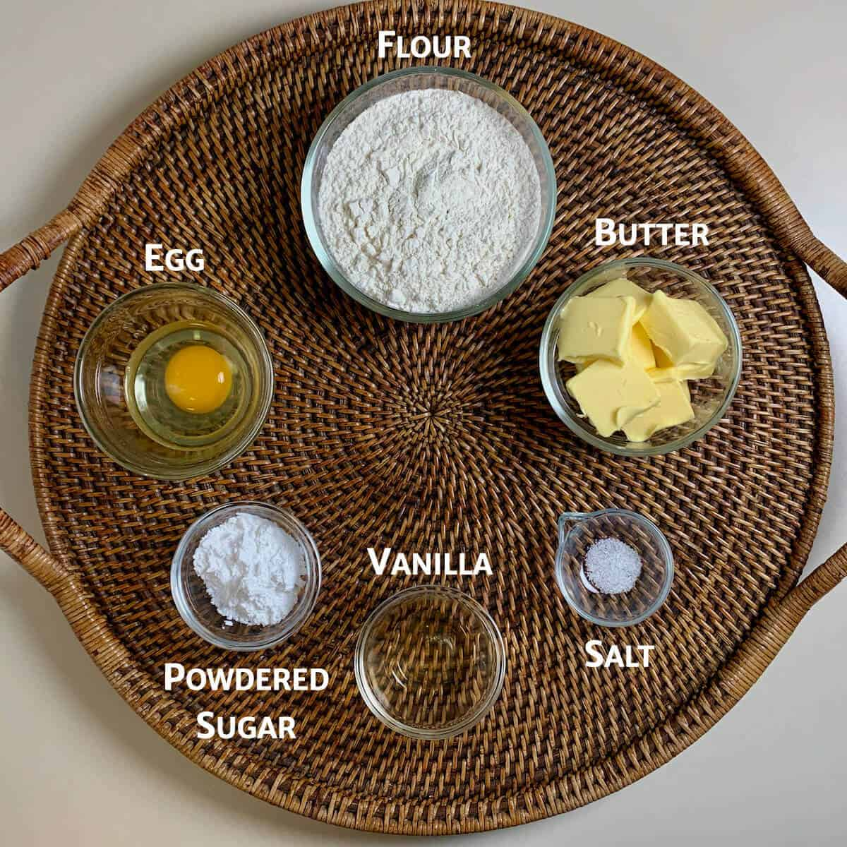 Shortcrust pastry ingredients on a wooden tray from overhead.