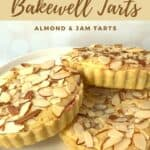 Three mini Bakewell tarts on a white cake stand Pinterest banner.