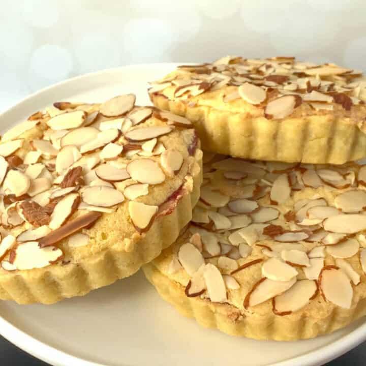 Three mini Bakewell tarts on a white cake stand.