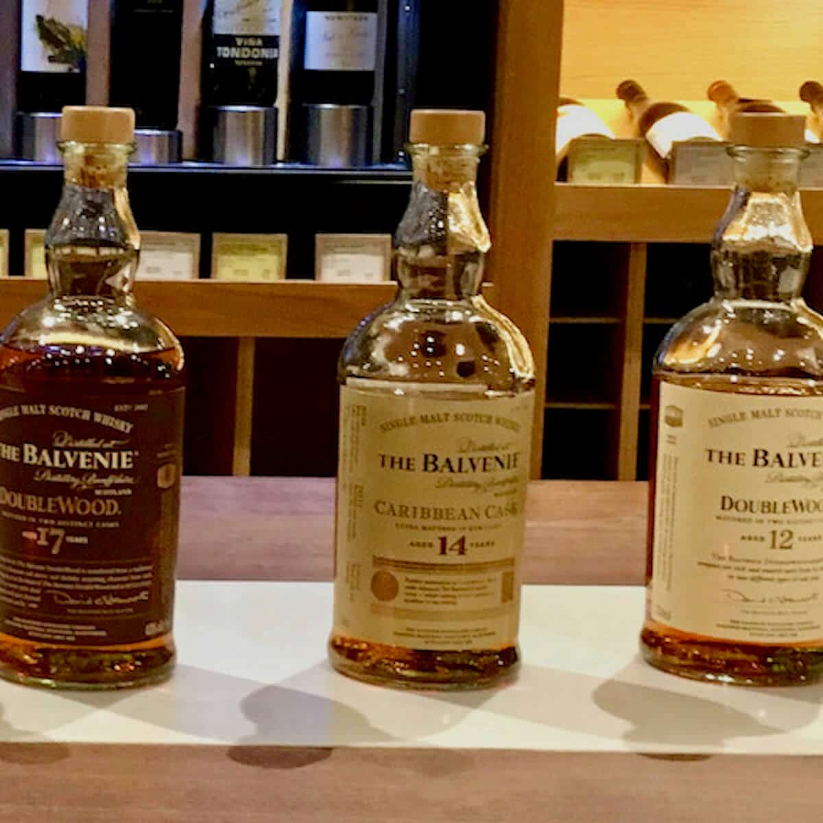 The Balvenie 12 year, 14 year, and 17 year lineup bottles on a counter.